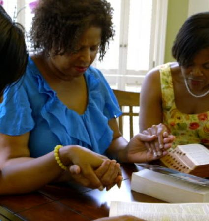 Three lovely African American women hold hands in prayer during Bible study time.